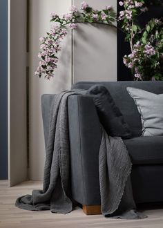 Stunning Scandinavian living room designed by Daniella Witte | Cherry blossoms adds a pop of colour and a lush summery feel |  Dark grey mid-century style sofa | IKEA Stockholm sofa with a Bemz cover in Graphite Simply Linen