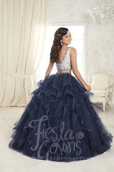 Choose this modern two-piece gown with a long ruffled skirt made from organza ball with horsehair edging, scattered with lace appliqués. Download the Fiesta Gowns by House of Wu sizing chart here. *No