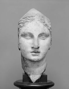 Athena (?). The head and neck were made separately for insertion in a statue. Above and on both sides of the face, the marble terminates in four planes with fairly smooth surfaces. The back of the head was omitted, and the surface at the back has been left rough. The lower lip and the hair above the left temple were slightly injured, and the surface has suffered from cleaning with acid. Scientific Analysis:  Harvard Lab No. HI217.