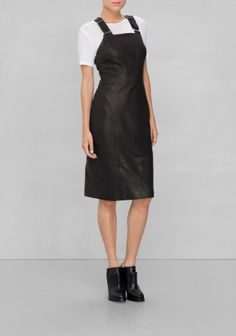 Exquisitely tailored, this luxe leather dress has a body hugging fit, intriguing seam details and a flattering knee-brushing length.