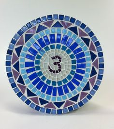 """A palavra """"Chakra"""" vem do Sânscrito e significa """"roda de luz"""". Os Chakras são centros de energia, que representam os diferentes aspectos da natureza sutil do ser humano. São eles: corpo físico, emocional, mental e energético. Os sete principais Chakras ficam localizados ao longo da coluna vertebral do corpo humano e, segundo a Tradição Hindu, seguem as cores do arco-íris. <br> <br>Essa mandala em mosaico tem o símbolo do chakra Frontal ao centro que representa a mente e a intuição. A função… Mosaic Bathroom, Bmw Logo, Flower Vases, Ems, Diy And Crafts, Pattern, Inspiration, Image, Chakra Symbols"""