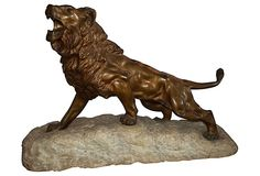 A bronze lion standing on a large piece of stone. Unsigned.