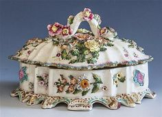 <b>A 19th century English porcelain shaped oval lidded dish</b> <br /> the deeply curved serpentine sides and lid heavily encrusted with sprays of flowers and foliage, the domed lid surmounted by a twisted tree branch with similar decoration, the base raised by the exaggerated shaped sides terminating in many feet, the interior of the base moulded with a compressed scallop shell design, 5 1/2in. (14cm.) high, 10in. (25.5cm.) long, broken and restored. <br />