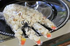 Witches' hands can be made by filling food handler gloves with popcorn. Use an almond or candy corn for fingernails, tie them off with a string, and add a spider ring to give them that spooky touch. Source: Toni Spilsbury