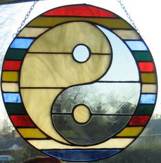 Yin yang; clockwise yin on top, surrounded by enso; multi-colored stained glass horizontal pieces