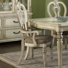 """Add classic appeal to your dining room or breakfast nook with this wood arm chair, showcasing raised acanthus leaf detailing and fluted front legs.        Product: ChairConstruction Material: WoodColor: Antique ivory and silverFeatures:  Silver tipped Fluted front legsDimensions: 44"""" H x 22"""" W x 24"""" DNote: Table and accents not included"""