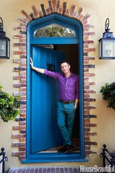 Peter Dunham: Dunham in the entry of his 1920s Tudor-style apartment. The door is painted Benjamin Moore Aura in Caribbean Blue Water.