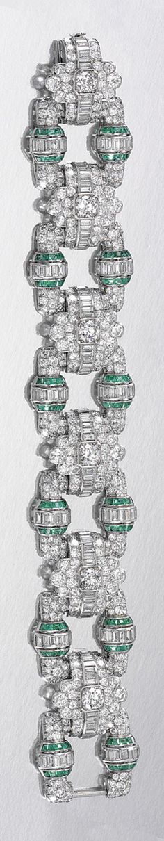 EMERALD AND DIAMOND BRACELET, 1930S.  Designed as a series of geometric links of stylised buckle design, interspersed with scalloped connecting links, set throughout with circular-, single-cut and baguette diamonds, highlighted with calibré-cut emeralds, length approximately 185mm, partially numbered, case by Asprey & Co Ltd, New Bond Street, London.