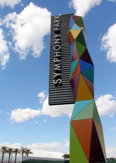 the new symphony park entrance sign sits at the west entrance of the new urban downtown development and lights up at night.  the sign is made up of plastic colored back-lit triangles and in the extruded lettering is highlighted with micro neon tubing on the sides of each letter.  symphony park is anchored by the cleveland clinics' lou ruvo center for brain health and the smith center for the performing arts, symphony park will be home to the city's most important civic, cultural and medical…