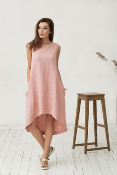 Hand crafted pure linen dress for women in soft pink colour. Made from a middle weight softened linen fabric this contemporary dress is a must for this summer. Breezy, easy draping, breathable, relaxed fit - perfect in the office or at the beach. Please note that the model is 175 cm height. If you are shorter, the dress will be longer accordingly.  Features:  - asymmetrical cut - sleeveless - knee length - two hidden side pockets - button closure at the back of a dress…