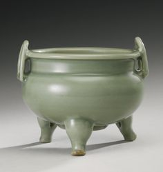 A 'LONGQUAN' CELADON TRIPOD CENSER  YUAN / MING DYNASTY the thickly potted globular body supported on three cabriole-shaped legs and surmounted by a short upright neck with everted rim applied on the shoulders with D-shaped loop handles, covered overall with a thick green glaze, the base pierced with a circular aperture and encircled by a thick unglazed ring, three spurs on the interior, wood cove