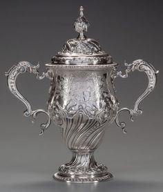 A WILLIAM GRUNDY GEORGE III SILVER LIDDED CUP, London, England, circa 1766-1767 -   Marks: (lion passant), (leopard's head crowned), WG, L  13 inches high - The double handled covered cup surmounted by a leaf finial over a stepped circular lid with etched grape and vine waist, tapering body and foot with chased stylized leaves, raised on a circular foot with gadroon edge.