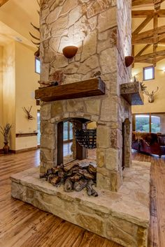 The wood-burning fireplace, with its four-sided design, is a highlight in the room. Reclaimed wood mantels and small sconces adorn the sides.