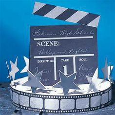 The Hollywood Clapboard Centerpiece features a black clapboard on silver film reel base with silver star accents.