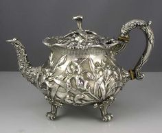 """A wonderful sterling silver tea pot by S Kirk & Son Co with chased irises all around the body and lid on four feet and three dimensional flower finial. The handle, lid and spout are also heavily chased. Height 7"""" at the finial; overall width 10"""". Extremely heavy i.e. 39.30 troy ounces. Circa 1903."""