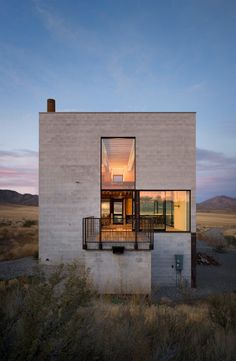 A remote concrete and glass shelter rises off the Idaho desert floor