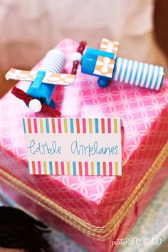 Edible Planes: USe push pop lollipops, wrapped them with patterned paper, attached sticks of gum as wings and glued on the accessories.