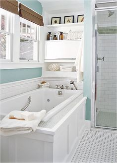 Bungalow-cottage bathroom with deep tub underneath window and neighboring shower.