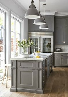 This timeless kitchen design is sure to inspire you to rejuvenate your cabinets with a coating of sleek grey paint. This kitchen combines white subway tiles and elegant marble countertops, just think of how stunning your brunch buffet and Nespresso coffee machine will look in the space!