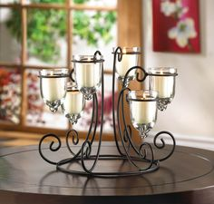 Let the candlelight shine bright from your tabletop with this stunning display. Six glass candle cups rest at different heights in a circular wrought iron stand that's embellished with scrolling flair. Place the candles of your choice inside and light the night with beauty.