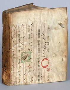 [1400-1500] Reliure en parchemin souple, probablement du XVe siècle, manuscrit à notations neumatiques, orné de lettrines rubriquées et d'une grotesque peinte en vert. Le parchemin a été utilisé en reliure essentiellement aux XVIe et XVIIe siècles. Le relieur a utilisé le parchemin de façon pour protéger l'ouvrage du jésuite Claude Thipaine, professeur de philosophie et de théologie à l'Université de Pont-à-Mousson.   Bibliothèque médiathèque Nancy, 5082