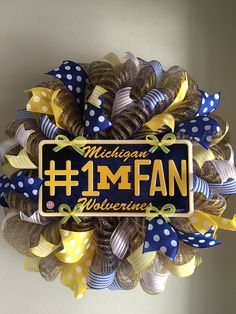 "Michigan Wolverines Mesh Wreath. This wreath is made on a blue and yellow striped mesh. It features a Michigan Wolverines #1 Fan centerpiece surrounded by lots and lots of blue, yellow and white wired ribbons. What a great way to show your support for your favorite team and to welcome your family and friends to your home. This wreath measures approximately 23"" in diameter."