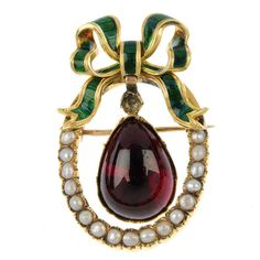 A late 19th century gem and enamel brooch. The pear-shape foil-back garnet, to the split pearl line and green enamel stylised bow surmount. Replacement gems and enamel. Length 4.5cms. Weight 11.7gms
