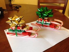 Candy cane sleds. You'll need candy canes, Kit Kat, Hershey's mini chocolates, ribbon, mini bows & a glue gun.