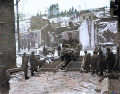 """""""During the Battle of the Bulge, a US Army half track crosses a temporary bridge over the Ourthe River, in the war-torn Belgian city of Houffalize, in January 1945."""" 16 January 1945: At 09.45, the 41st Cavalry of the 11th Armored Division made contact with the 41st Infantry of the 2nd Armored division in Houffalize, thus terminating the Bastogne Operation so far as the 3rd Army was concerned. (AP photo)"""