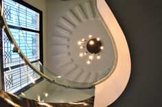 The semicircular pattern is extended in false ceiling adds luxuryness to the stairwell by A.J Architects. Curved Staircase, Neutral Palette, Gated Community, Common Area, Large Windows, Teak Wood, Luxury Interior, Architects, Facade