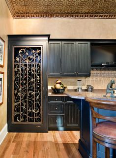 Chic Wine Cabinet in Modern Home Interior Design: Dark Painted Wine Cabinet With Glass And Engraved Iron Installed To Hide The Wine Bottles ...