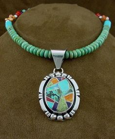 necklace from Silver Tribe by Navajo artist L. Begay.   The artist used sterling silver, turquoise, oyster shell, Gasperite, Mediterranean coral, blue opal, suguilite and purple coral to create the inlay design.