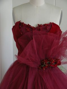Close up:  this beautiful 1950 vintage evening gown is made in such a wonderful deep rich burgundy velvet and tulle. It has velvet flower embellishments on the shelf bust and at the waist. Shelf bust also has gathered tulle and the bodice is all lined in burgundy taffeta.