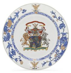 AN ARMORIAL PLATE  CIRCA 1735  The center with the arms of Sandilands quarterly impaling Hume, Pepdie, Polwarth and St. Clair, supported by a bluish-gray and a sepia and gilt lion, the crest shown twice on the rim between finely drawn flowering boughs in blue enamel, grisaille and gilt  9 1/8 in. (23.1 cm.) diameter