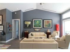 Grey gray contemporary living room with cream leather furniture and colorful artwork.  Park Shore in Naples, Florida