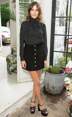 Alexa Chung pairs a silk polkadot blouse with a suede black skirt and black heels