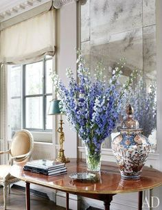 In a New York penthouse designed by Michael Smith, delphiniums in a William Yeoward crystal vase and an Imari porcelain lidded jar top a Directoire mahogany table from Gerald Bland.Pin it.