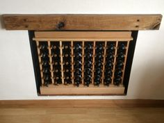 Small bespoke solid oak wine racking features individual bottle hole storage, built within an on fireplace with a plinth and top. Supplied by Wineware in the UK.
