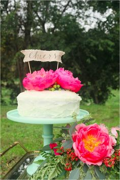 Very cute mint cake stand, and lovely big pink flowers decorating the cake.