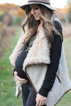 Fall maternity fashion in this fur and leather vest with a wool hat and riding boots.