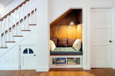 The bookshelves underneath the reading nook pull out like a drawer to reveal more storage. The door to the left leads to a secret hideout for the kids. The door on the right leads to the powder room. Farmhouse Staircase by JWT Associates