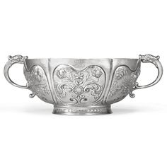 A Highly Important American Silver Punch Bowl, Cornelius Kierstede, New York, 1700-1710 the bowl divided into six curved panels, each chased with a lobate cartouche centered by boldly chased & engraved leafy floral sprays, one cartouche with flower bud resembling a dog's head, another with stem extending into an engraved long-beaked bird head, all with partly-matted &  pricked decoration...diameter approximately 12 1/4 in., length over handles 17 1/4 in. [Sold for 5,906,500 USD]