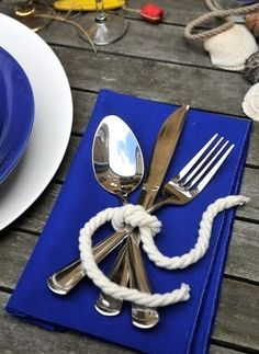 Fun nautical look. Blue napkin with utensils spread, gently tied together with white rope complement the bold, contrasting plates.