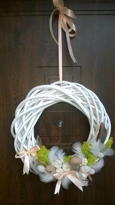 Bialy wianek dekoracyjny na drzwi. Wielkanocne dekoracje. Kokardki, piórka, jajeczka.