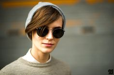 Grey beanie, Ray-Ban Round sunglasses, white shirt and a crew neck sweater.