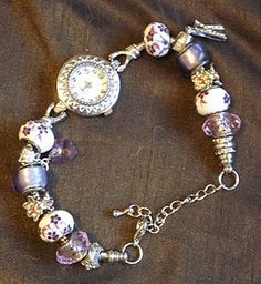 The lastest craze is these charm bracelet watches and they sell for £100 plus!!! I made my own at a fraction of the cost and although the picture doesn't do it justice, it is really pretty and sparkly with crystals all around the watch face and purple tone pandora beads and a crystal initial and Swarovski violet heart charm.