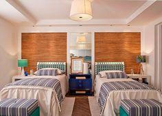 A designer de interiores Patrícia K Pasquini escolheu as cores azul e verde para decorar o quarto de hóspedes de uma mostra de decoração. Atrás das camas, palha de bananeira e seda natural revestem a parede. O ambiente, de aproximadamente 30 m², leva revestimento vinílico da Tarkett no piso.