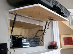 hinged TV compartment to hide electronics and cords behind television, use IR remote (via Apartment Therapy)