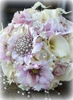 Soft pink artificial brides bouquet - stunning design with lots and lots of embellishments : We have used sensational dusky pink silk anemones and mixed them with ivory and complimenting dusky pink roses, calla lilies and frosted ivory berries to create a one off bouquet that certainly has the WOW factor! A selection of diamante brooches embellish this stunning bouquet, the central anemone having a large diamante brooch centre, we have also used diamante and crystal stems as well as delicate…