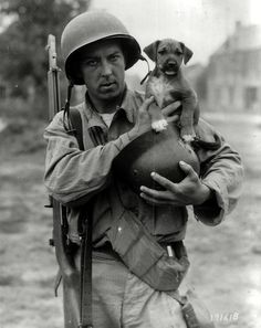 """Pfc Joseph E. Day holds a puppy named """"Invasion"""" in a German helmet, Le Dezert, France, 1944"""
